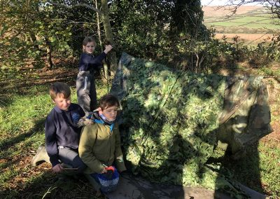 Boys building a den at the WIld Warriors forest school in Cornwall