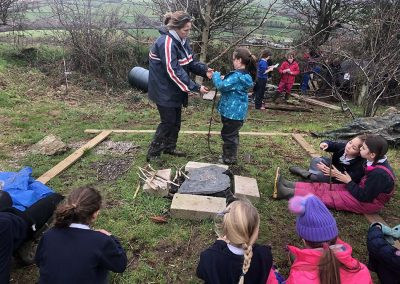 Girl practising tying knots at the Wild Warriors forest school Cornwall