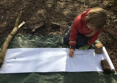 A young child drawing in woodland at the Wild Warriors Forest School Cornwall