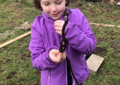 A girl is showing off the knot she has managed to tie at Wild Warriors Forest school in Cornwall