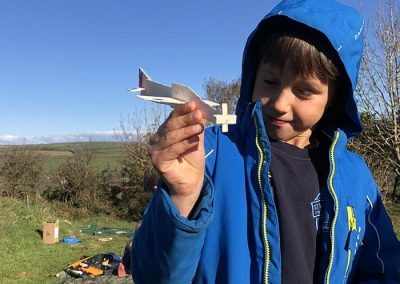 A boy showing off the wooden aeroplane he had made at Wild Warriors forest school in Cornwall