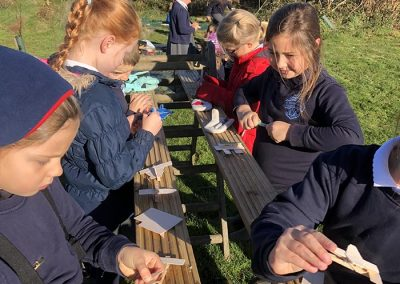 A group of children making wooden aeroplanes at Wild Warriors forest school Cornwall