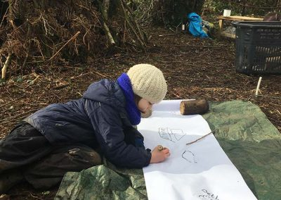 A girl with a very large sheet of paper laying on the woodland floor and colouring