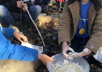 Children with sticky fingers making a dough to cook on the campfire with Wild Warriors Forest School