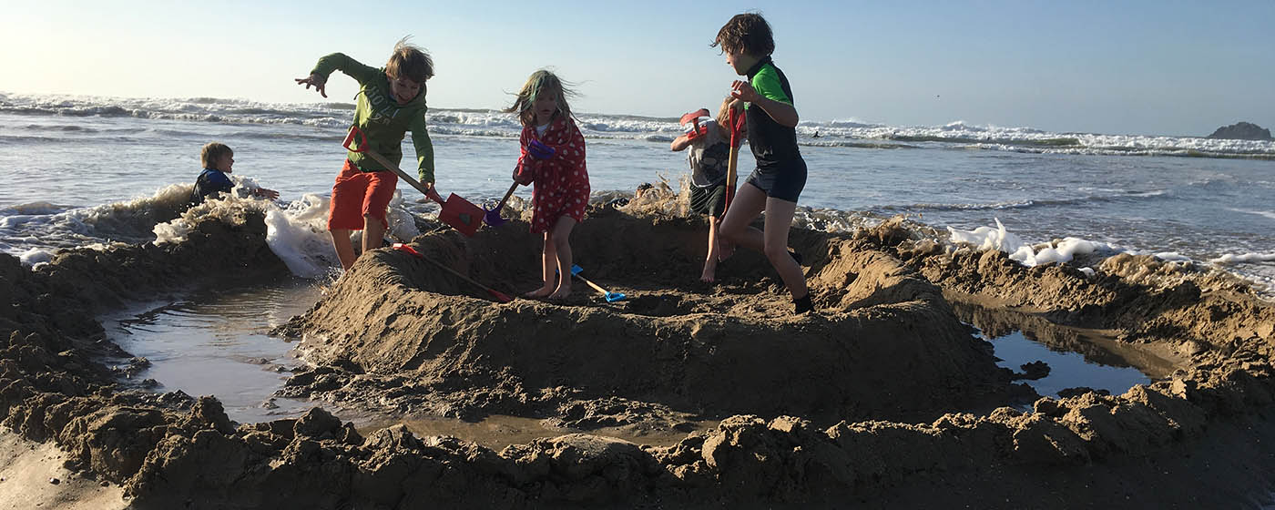 Children playing on Polzeath beach Cornwall during a Wild Warriors adventure
