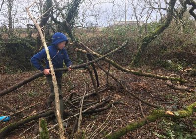 A boy gathering branches to make a shelter with Wild Warriors Forest School