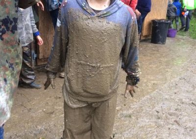 A smiling girl who is covered from head to foot in mud stood on muddy ground at Wild Warriors forest school in Cornwall