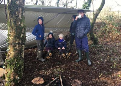 Group of children having a rest under a temporary shelter at Wild Warriors Forest School in Cornwall