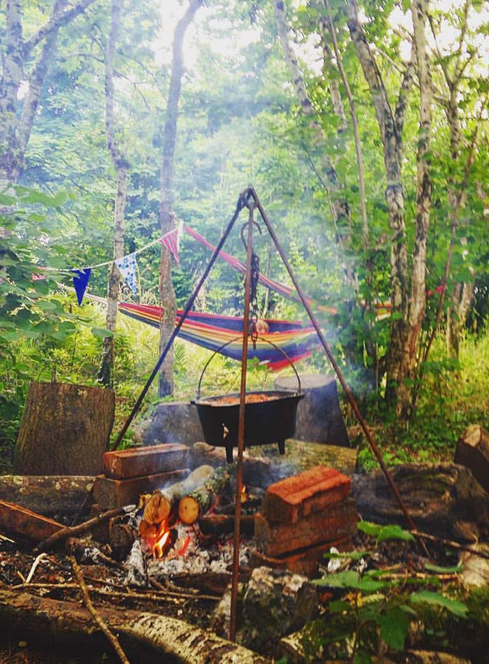 Camp fire and colourful hammock set up ready for a Wild Warriors adventure